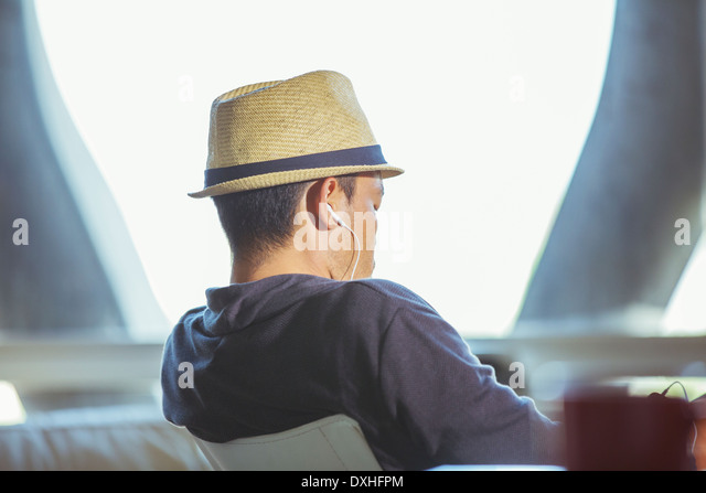 Man in fedora wearing headphones - Stock Image