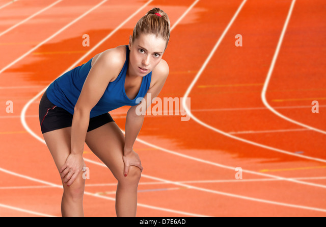 Female jogger resting after a long run on a wet athletics running track - Stock Image