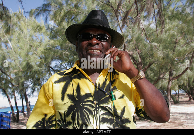 Grand Turk Cockburn Town Columbus Landfall National Park Governor's Beach Black male cell phone - Stock Image