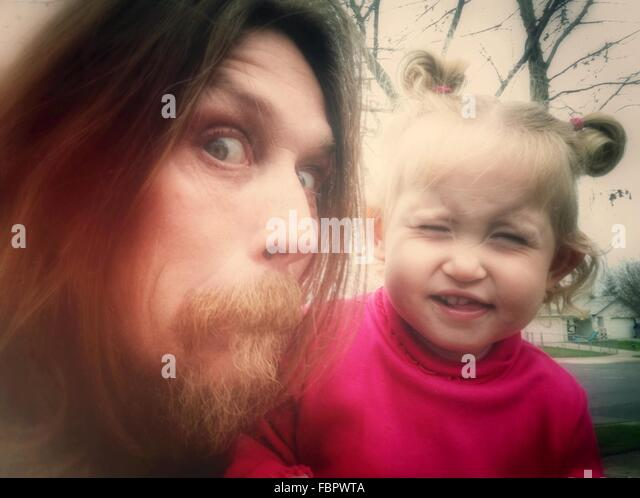 Close-Up Portrait Of A Man And Baby Girl Making Faces - Stock Image