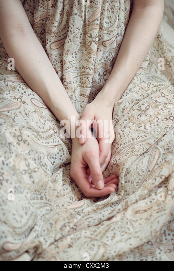 Close up photo of hands in the lap of a girl wearing a light summery dress - Stock-Bilder