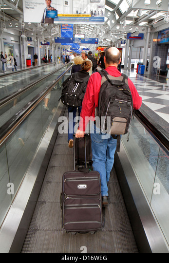 Chicago Illinois O'Hare International Airport ORD concourse gate area terminal passengers luggage moving sidewalk - Stock Image