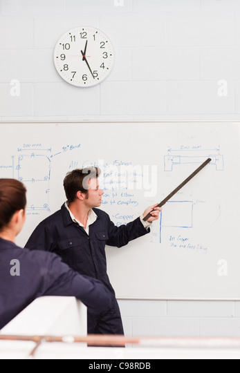 Professional plumber teaching apprentice front whiteboard - Stock Image