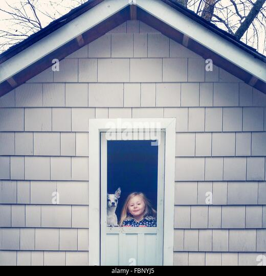 Portrait Of Cute Little Girl With Pet Dog At Front Door Of House - Stock Image