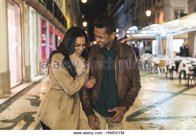 Couple walking arm in arm through city, at night, Lisbon, Portugal - Stock-Bilder