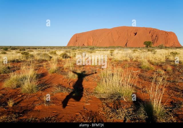 Australia, Northern Territory, Uluru-Kata Tjuta National Park. Shadow jumping for joy at Uluru (Ayers Rock) at sunset. - Stock-Bilder