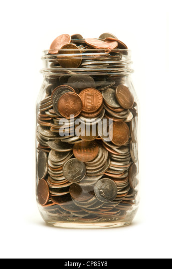 Glass jar almost overflowing with American coins against a white background - Stock Image