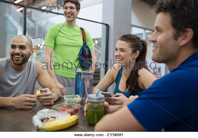 Friends talking and eating lunch at gym - Stock Image