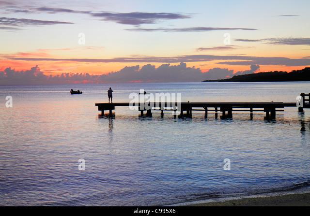 Curaçao Netherlands Antilles Dutch Piscadera Bay Caribbean Sea pier man standing rowboat coastline sunset twilight - Stock Image