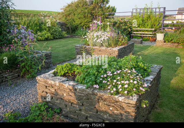Dry stone walls garden stock photos dry stone walls for Red rock for flower beds