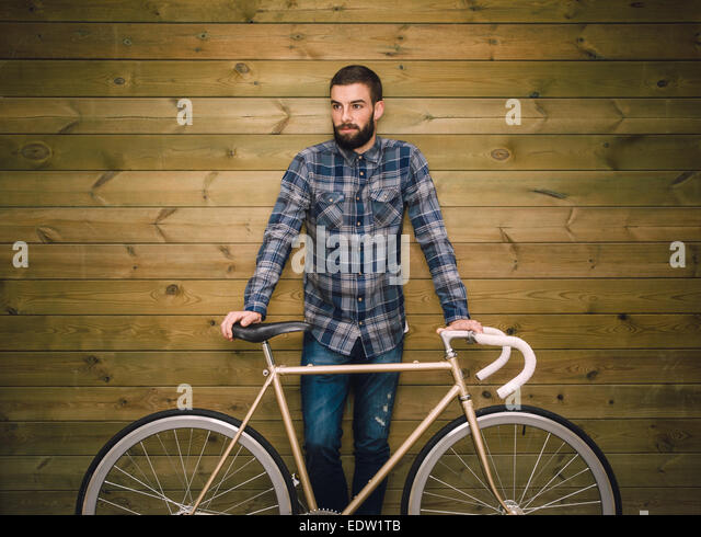Hipster man with his fixie bike on a wooden background - Stock-Bilder