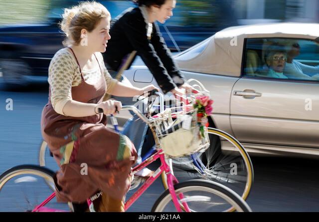 Charleston South Carolina Broad Street woman women young old car cyclist bicycle bike car basket exercise alternative - Stock Image