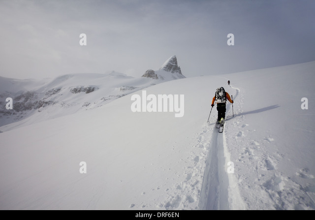 Alberta Canada. Two skiers ascending ridge in mist and cloud Wapta Traverse - Stock Image