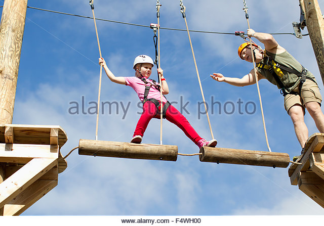 Father and daughter (6-7) climbing - Stock Image