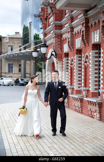 The happy newlyweds on a walk through the city - Stock Image