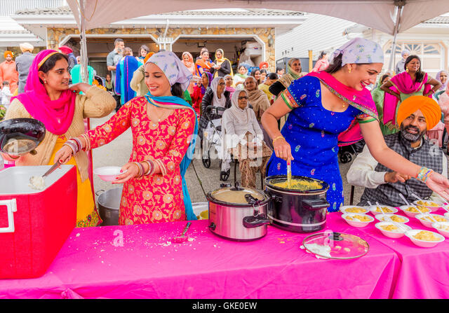 Free food is happily dispensed by members of the BCGEU at the Vaisakhi Parade and Celebrations, Surrey, British - Stock Image
