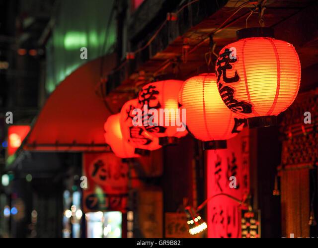 Red Illuminated Chinese Lanterns Hanging Outside Shop At Night - Stock Image