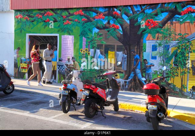 Florida Key West Florida Keys Bahamas Village Petronia Street mural Black man motor scooters parked woman - Stock Image