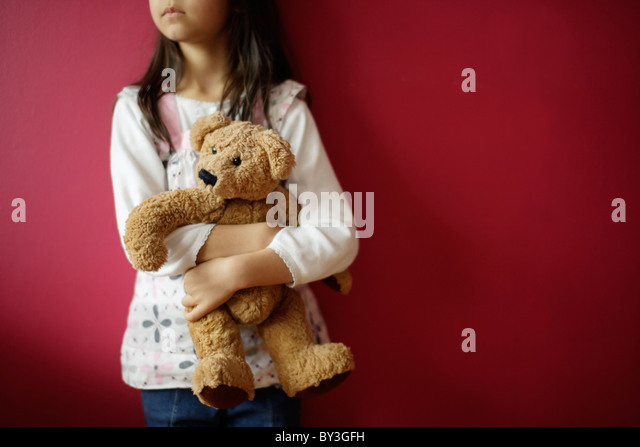 Girl holds teddy bear - Stock Image