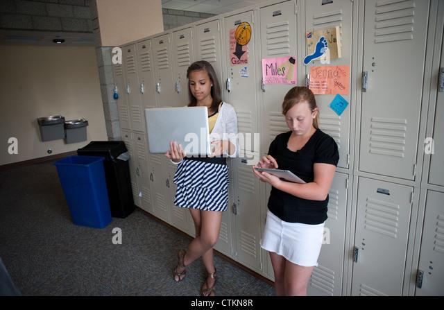 Teenage girls using ipad and laptop in middle school hallway. - Stock Image