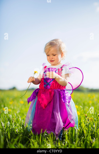 Girl in fairy costume playing in field - Stock Image