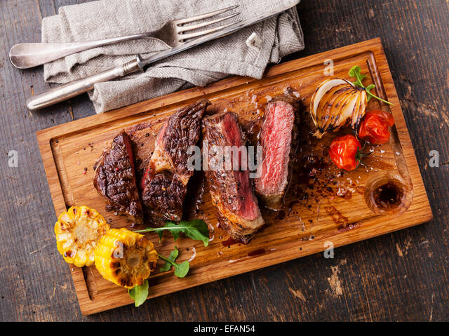 Sliced medium rare grilled Beef steak Ribeye with corn and cherry tomatoes on cutting board on wooden background - Stock Image