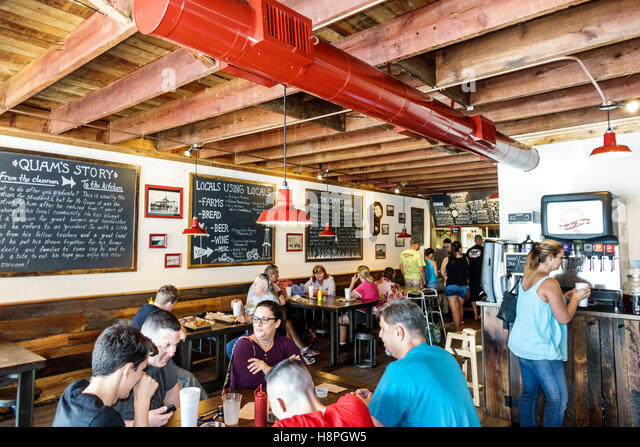 Florida Titusville Quam's Schoolhouse Burgers & Grinders restaurant inside tables family exposed ceiling - Stock Image