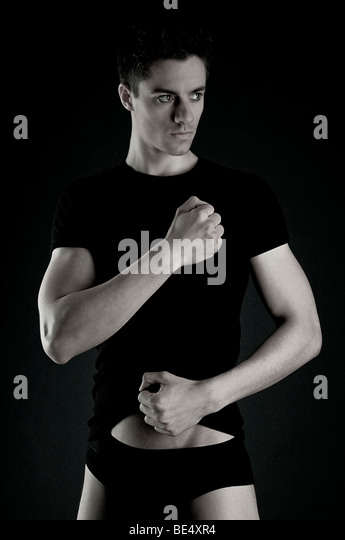 Young man, black clothes, arms tense, looking to the side - Stock Image