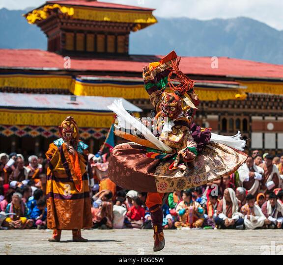 Dance of terrifying deities (Tungam) with spectators in the background Paro religious festival Bhutan - Stock-Bilder