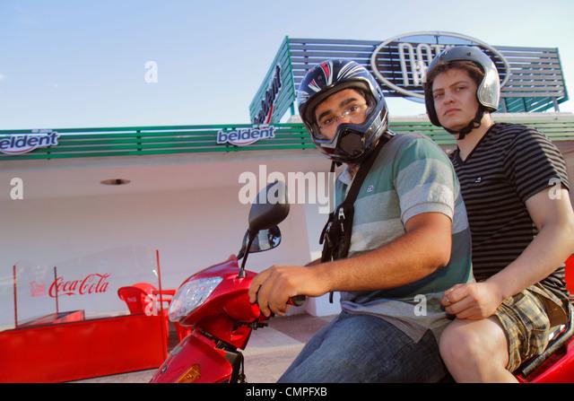 Uruguay Montevideo Rambla Republica de Chile street scene Hispanic man helmet motor scooter motorcycle bike passenger - Stock Image