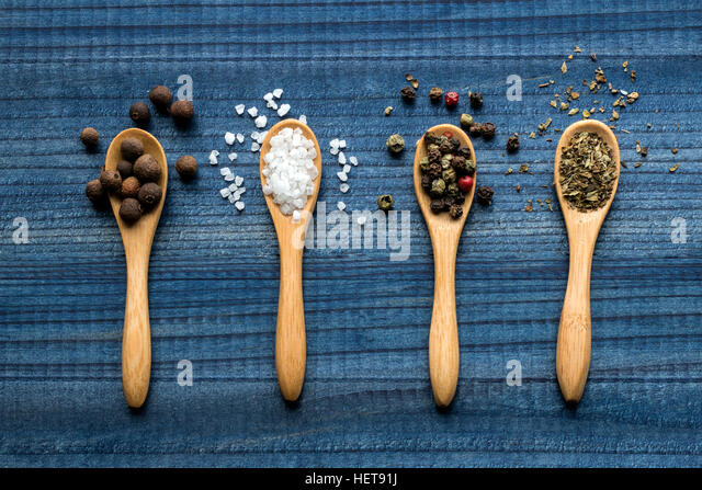spices on wooden spoons on blue wooden table - Stock Image