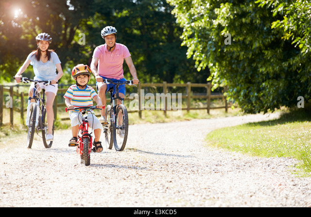 Asian Family On Cycle Ride In Countryside - Stock Image