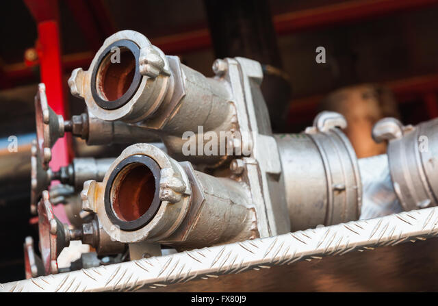 Firefighting equipment on red fire truck. Water hydrants close-up photo with selective focus - Stock Image