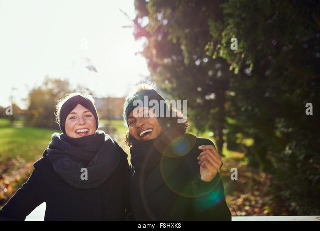Two smiling women standing on bridge in park.Sunny - Stock Image