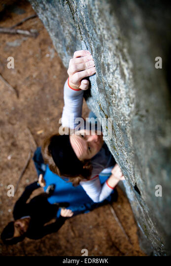 A female rock climber reaches out while on a boulder climb in Pemberton, British Columbia, Canada. - Stock Image