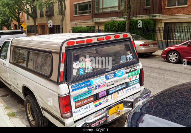 Leftie parked truck covered in protest stickers representing various causes. - Stock Image