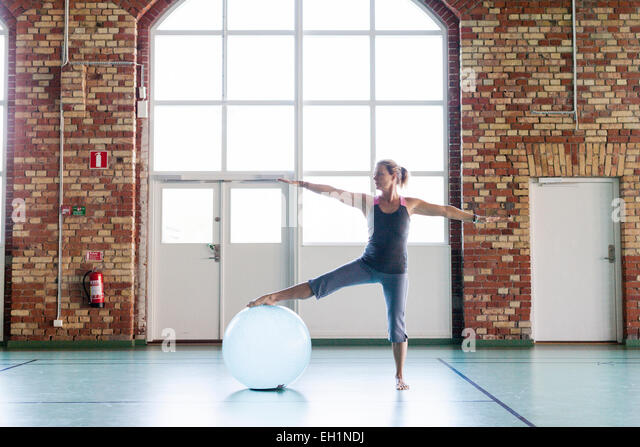Full length of woman exercising with fitness ball in health club - Stock Image