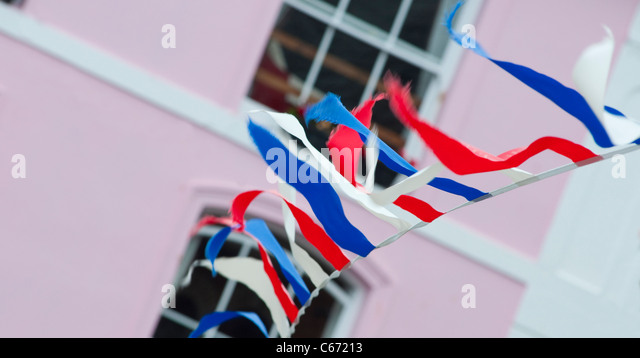 Bunting hanging in a street in the Cornish town of Fowey, Cornwall, England. - Stock Image