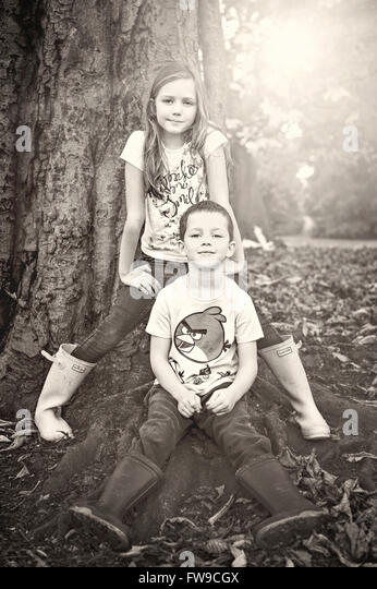 two children posing in park at the big tree - Stock Image