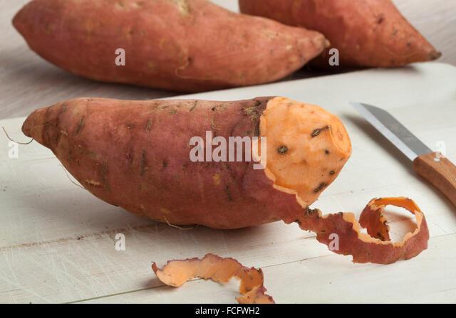 Partially peeled fresh sweet potato - Stock Image