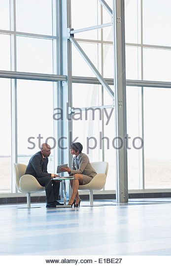 Business people with digital tablet in modern lobby - Stock Image