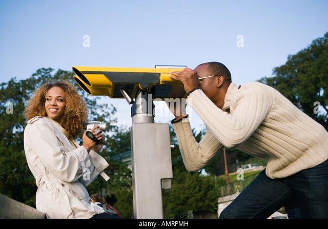 Tourist peering through large viewing binoculars - Stock-Bilder