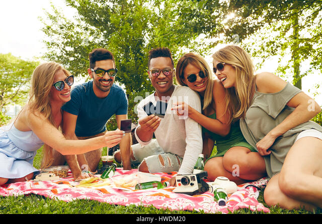 Five adult friends looking at film from instant camera at picnic in park - Stock-Bilder