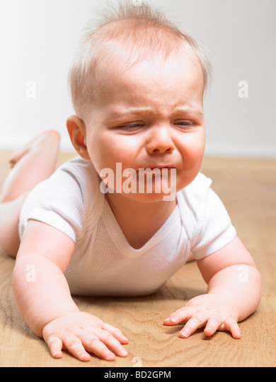 Baby crying on the floor - Stock Image