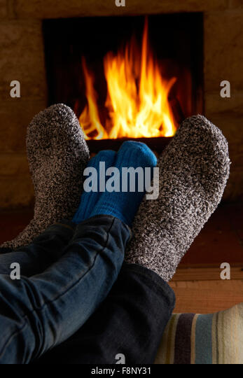 Father And Child Warming Feet By Fire - Stock Image