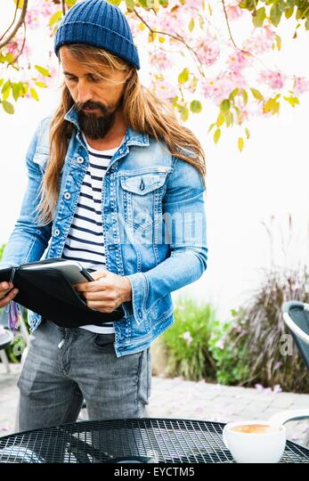 Mid adult man putting laptop in case - Stock Image