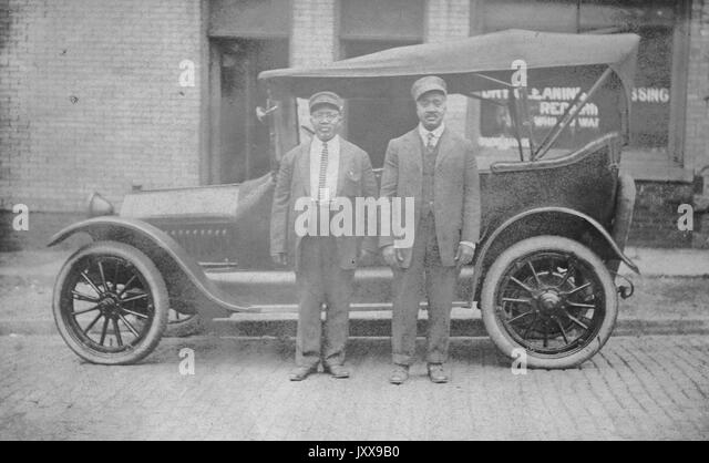 Two African American men wearing suits and hats in front of a car, in front of a dry cleaning shop, neutral facial - Stock Image