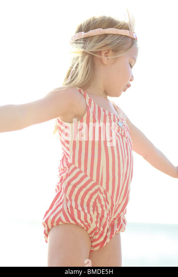 Young girl in striped bathing suit - Stock Image