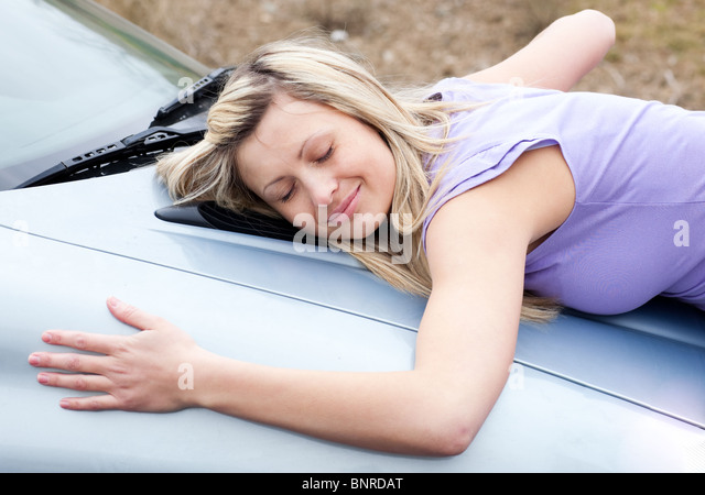 Cheerful female driver huging her new car - Stock Image