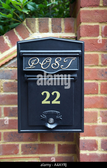 black letter box on red brick wall - Stock Image